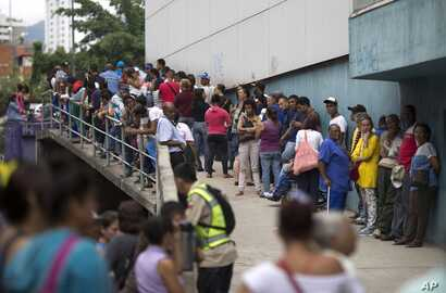 People wait outside a supermarket to buy government subsided food in Caracas, Venezuela, Nov. 18, 2016. As domestic production dries up in Venezuela, the state has given itself the role of importing nearly all the country's food.
