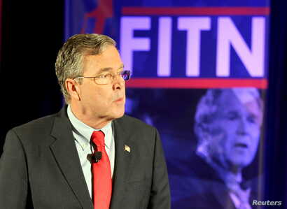 FILE - U.S. Republican presidential candidate Jeb Bush stands in front of a photo of former president and brother George W. Bush as he speaks at the New Hampshire GOP's FITN Presidential town hall in Nashua, New Hampshire, Jan. 23, 2016.