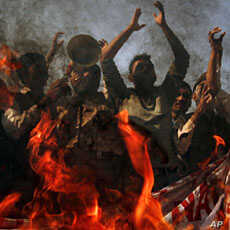 Protesters yell anti-American slogans while burning a poster of Pakistan Prime Minister Yousuf Raza Gilani, to condemn the government's support of the U.S., Multan, November 29, 2011