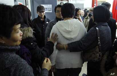 Yan Tao Chen, third from left,  waits for his wife Su Zhen Chen, center, as she is assisted following a news conference on Thursday, Jan. 5, 2012 in New York.  The Chen's provided an update on a Pentagon investigation into the death of their some Dan