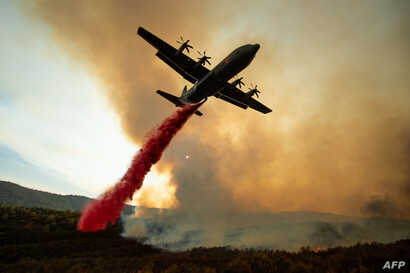 An air tanker drops retardant on the Ranch Fire, part of the Mendocino Complex Fire, burning along High Valley Rd near Clearlake Oaks, California.