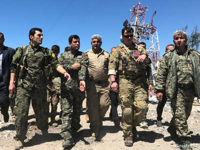 A U.S. military commander, second from right, walks with Kurdish fighters from the People's Protection Units (YPG) at the YPG headquarters that was hit by Turkish airstrikes in Mount Karachok near Malikiya, Syria, April 25, 2017.