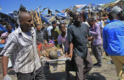 Somali men retrieve the dead body of a person who was killed when a car bomb targeted a police station in the Waberi neighborhood, where President Hassan Sheikh Mohamud was visiting a university, in the capital Mogadishu,  Saturday, Nov. 26, 2016.