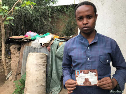 Abedir Jamal holds the identification card of his late brother Obsa Jemal, who was killed in anti-government protests, during a Reuters interview in Harar, Ethiopia, July 22, 2018.