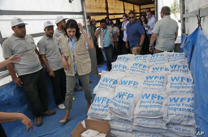 U.S. Ambassador Nikki Haley, center left, walks past food parcels provided by the World Food Program, part of the humanitarian aid shipments into Syria, during a visit at the Reyhanli border crossing with Syria, May 24, 2017.