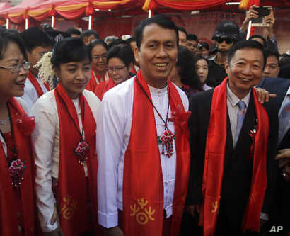 Phyo Min Thein, second from right, Yangon region chief minister, smiles as he takes part in cerebrations to mark Lunar New Year along with local Chinese at Chinatown, Jan. 28, 2017, in Yangon, Myanmar.