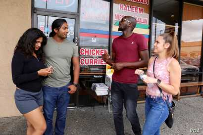 Left to right: Friends Hinna Akhtar, Abdulla Kudrath, Shannon Washington and Samantha Graiza share an Indian and Pakistani meal at Himalaya Restaurant in Houston, Texas. (R. Taylor/VOA News)