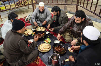 Pakistani customers eat grilled meat at the Charsi (Hashish) Tikka restaurant in Namak Mandi in Peshawar, Dec. 6, 2018.