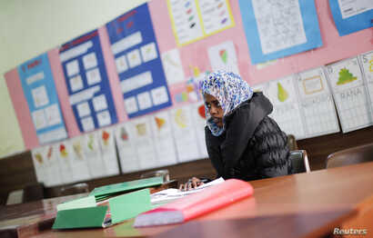 FILE - Amina, a migrant from Somalia, studies Italian at a school in Riace, Calabria region, Italy, Nov. 22, 2013.