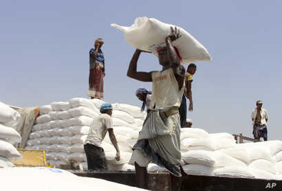 FILE - In this Sept. 21, 2018 photo, men deliver U.N. World Food Programme (WFP) aid in Aslam, Hajjah, Yemen.