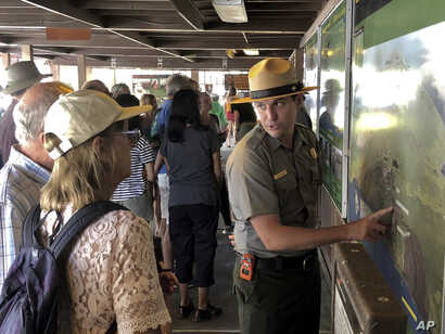 Tourists get directions from a park ranger on Sept. 22, 2018, the first day Hawaii Volcanoes National Park is reopened after volcanic activity forced the park to close for more than four months in Hawaii.