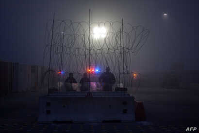 Members of the U.S. Border Police guard the international bridge in Texas, as seen from Piedras Negras, Coahuila state, Mexico, Feb. 6, 2019.