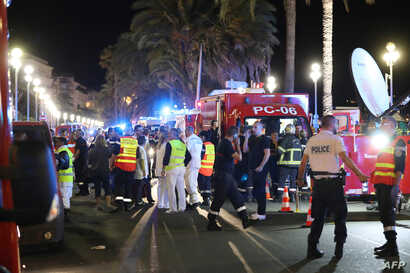 Police officers, firefighters and rescue workers are seen at the site of an attack on July 15, 2016, after a truck drove into a crowd watching a fireworks display in the French Riviera town of Nice.