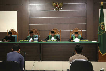 Two men accused of having gay sex sit on the defendants' chairs during their trial at Sharia court in Banda Aceh, Indonesia, May 10, 2017.
