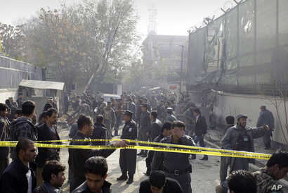 Afghan security men and media members gather at the scene of a suicide attack in Kabul, Afghanistan, November 21, 2012.