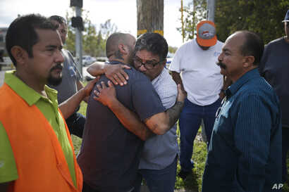 Jesus Gonzales, center left, who has been separated with his wife since Wednesday's shooting, is comforted by local church members including Jose Gomez, center right, Dec. 3, 2015, in San Bernardino, Calif.