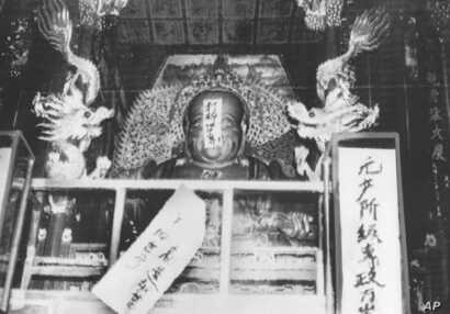 "FILE - In this file photo taken Aug. 27, 1966, a Buddha statue is covered with signs reading ""Destroy the old world,"" and ""Establish a new world,"" by ultra-patriotic Red Guard who reject ancient Chinese traditions at Lin Yin temple in Hangzhou, easte..."
