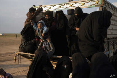 Women and children exit the back of a truck, part of a convoy evacuating hundreds out of the last territory held by Islamic State militants, in the desert near Baghuz, eastern Syria, Feb. 22, 2019.