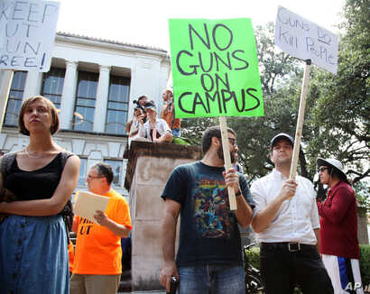 Students holds signs and sex toys as they protest a campus carry law in Austin, Texas, Aug. 24, 2016.