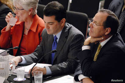 FILE - Dr. Scott Gottlieb, center, appeared as an American Enterprise Institute resident fellow when he participated in a hearing on health care reform before the Senate Health, Education, Labor and Pensions Committee on Capitol Hill in Washington, J...