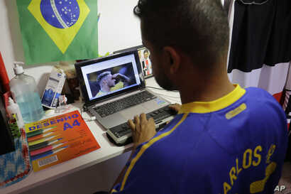 Carlos Junior, who is both deaf and blind, uses a braille display to read soccer news as he prepares to leave his home to follow the World Cup match between Brazil and Mexico in Sao Paulo, Brazil, July 2, 2018.