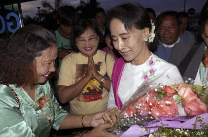 Myanmar's opposition leader Aung San Suu Kyi, right, receives flowers from a supporters of her National League for Democracy Party upon her arrival at Yangon International Airport to depart for China, Wednesday, June 10, 2015.