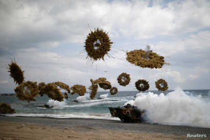 FILE - Amphibious assault vehicles of the South Korean Marine Corps fire smoke bombs as they come ashore during a U.S.-South Korea joint landing operation drill as a part of the two countries' annual military training called Foal Eagle, in Pohang, So...