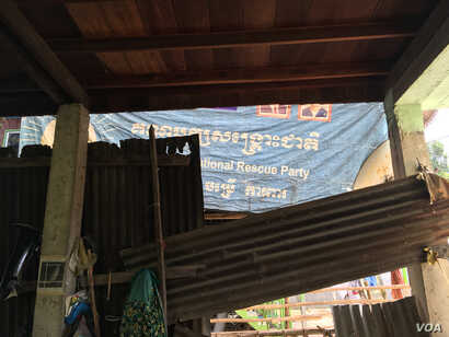 After the opposition party was dissolved, Keo Eat was ordered by police to take down from his home all the banners bearing its logo. He complied but turned one inward as a gesture of defiance, Nov. 27, 2017.