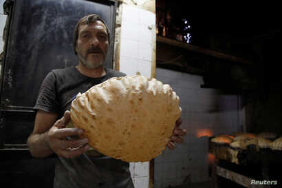 A man poses with a loaf of bread inside a government bakery in Damascus, Syria, Sept. 17, 2016.