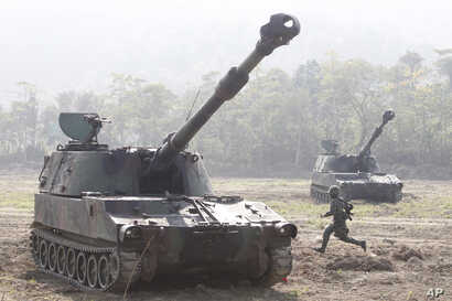 A soldier runs to an M109 tank during military exercises at the Chukeng area in Taichung county, Taiwan, Jan. 17, 2017. Singapore and Taiwan will continue to carry out a military training program begun in 1975.