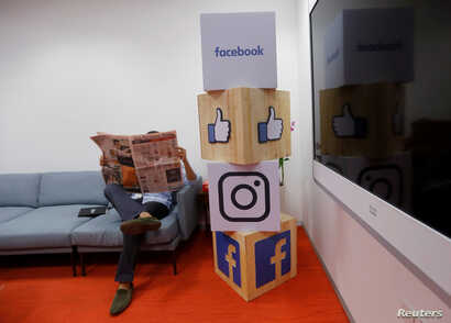 FILE - A man reads a newspaper at the reception area of Facebook's new office in Mumbai, India, May 27, 2016.