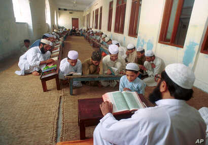 FILE - An undated photo of Pakistani children studying the Quran at a religious school in Lahore, Pakistan.