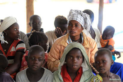 Mothers and children, refugees from from Democratic Republic of Congo, wait to be registered by UNHCR personnel, in Ntoroko, Uganda, Feb. 17, 2018.