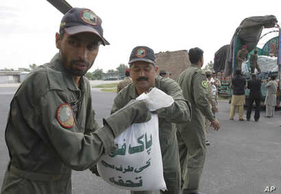 Pakistani soldiers load relief goods to a plane for earthquake victims, in Peshawar, Pakistan, Oct. 27, 2015.