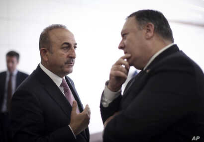 Turkey's Foreign Minister Mevlut Cavusoglu, left, talks with U.S. Secretary of State Mike Pompeo at the Esenboga Airport in Ankara, Turkey, Oct. 17, 2018.
