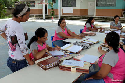 Teachers organize students' files on the first day of school, in Caucagua, Venezuela, Sept. 17, 2018.