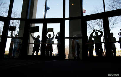 FILE - People who could not get into the event because of space limits hold signs outside a town hall meetingin North Charleston, South Carolina, Feb. 25, 2017.