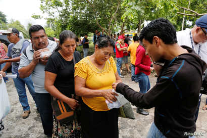 Relatives of victims of the eruption of the Fuego volcano receive food from volunteers outside the morgue in Escuintla, Guatemala, June 7, 2018.