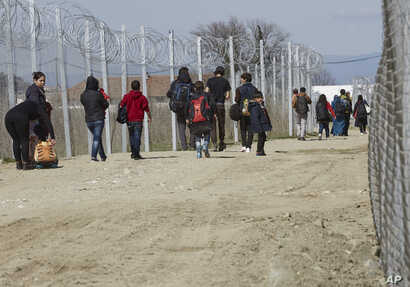 Migrants walk to registration and transit camp after entering Macedonia from Greece near the southern Macedonian town of Gevgelija, Saturday, March 5, 2016.