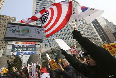 FILE - South Korean protesters wave U.S. and South Korean flags at a rally to support the deployment of THAAD, an advanced U.S. missile defense system, Feb, 15, 2017.