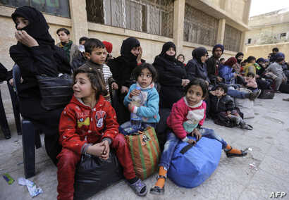 A picture taken on March 13, 2018 shows evacuated civilians and children sitting in the yard of a school lying on the government side of the Wafideen checkpoint on the outskirts of the Syrian capital Damascus neighboring the Eastern Ghouta enclave.