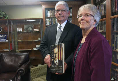 Arthur Young, left, and his wife, Pat, hold one of the 2,744 books about U.S. presidents he donated to the New Hampshire Political Library, part of the New Hampshire Institute of Politics at Saint Anselm College in Manchester, New Hampshire, June 9, ...