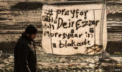"FILE - A man walks past a banner reading ""Pray for Deir Ezzor"" at the migrant camp known as the ""Jungle"" in Calais, France, Dec. 7, 2015."