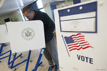 FILE - A voter casts his ballot behind a ballot booth during the U.S. presidential election at a polling station in the Staten Island Borough of New York, U.S.