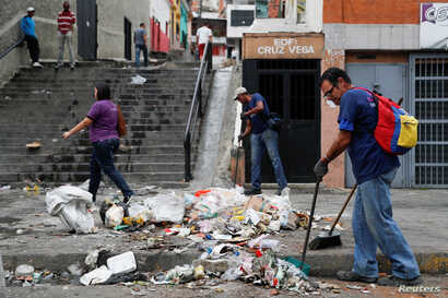 Workers clean the street after a protest in Caracas, Venezuela, Jan. 24, 2019.