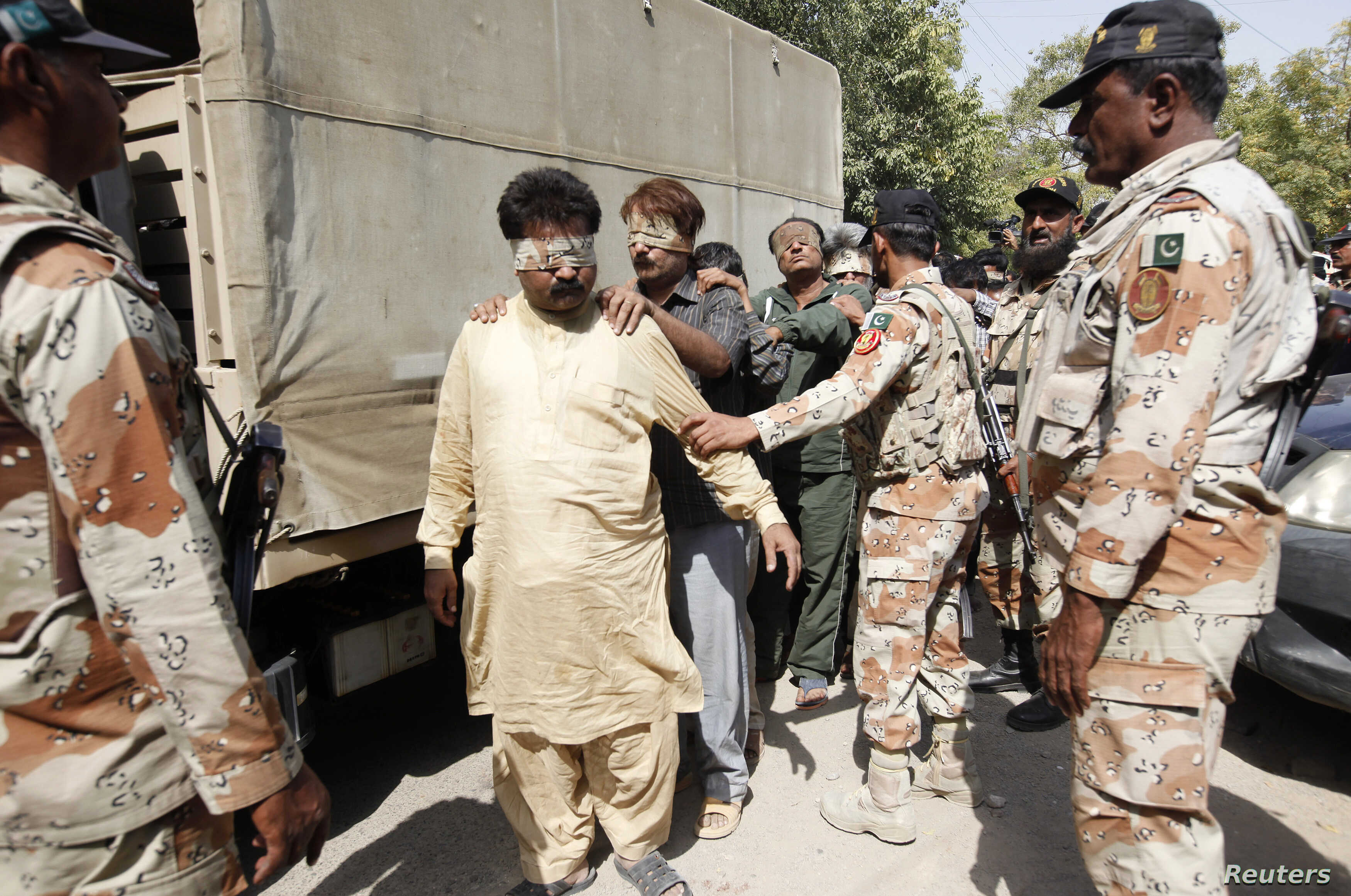 FILE - Paramilitary soldiers escort blindfolded men, detained during a raid, to be delivered to an anti-terrorism court in Karachi, Pakistan, March 12, 2015.