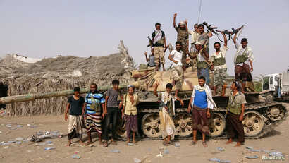 Tribal fighters loyal to the Yemeni government stand by a tank in al-Faza area near Hodeida, Yemen, June 1, 2018.