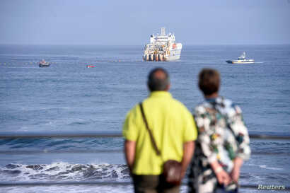 FILE - A couple observe a cable-laying ship at Arrietara beach, near Bilbao, northern Spain, June 13, 2017, as Facebook Inc. and Microsoft Corp. join forces to build an underwater fiber-optic cable across the Atlantic Ocean, linking Europe and the U....