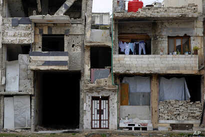 A family that returned to live in their apartment inside a heavily damaged building hang their clothes on a balcony in the Bab Dreib neighborhood of Homs, Syria, Jan. 17, 2018.