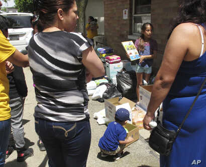 FILE - A boy picks out a soccer ball from donations delivered to an Ohio trailer park in Norwalk, Ohio, June 15, 2018. Community members donated diapers, baby wipes, food and clothing for the families of workers arrested in an immigration raid at a g...